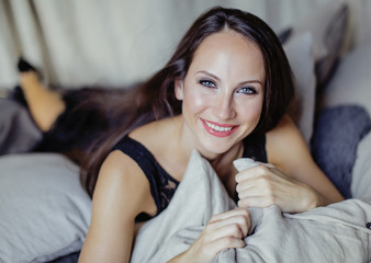 pretty young brunette woman in bedroom interior smiling