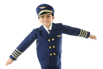 An elementary boy in a pilot's uniform, happily pretending to fly with his arms spread like wings.