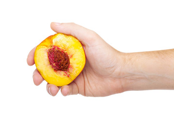 hand with a fresh juicy peach split in half isolated on a white