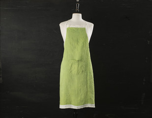 Green Kitchen Apron On Mannequin Over Black Background