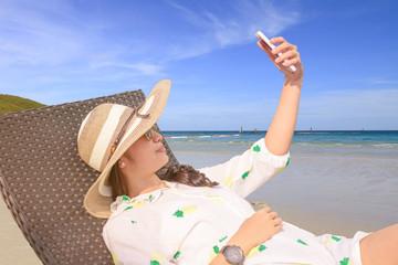 Beautiful Asian girl selfie with smartphone on bench near beach.