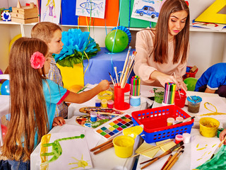 Kids with young beautiful teacher woman painting on paper at table  in  kindergarten .
