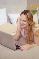 glückliche frau liegt auf dem bett und schaut auf ihren laptop