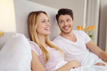 glückliches paar sitzt entspannt im bett und genießt die freie zeit