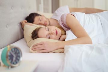 schöne frau liegt mit ihrem mann im bett und schläft
