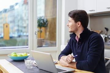nachdenklicher mann arbeitet zuhause am laptop