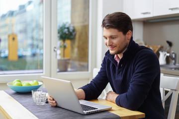 mann sitzt zuhause am tisch und liest eine nachricht am laptop
