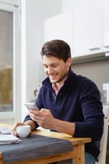 lächelnder mann liest eine nachricht am mobiltelefon
