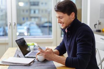 mann sitzt am küchentisch und schaut auf sein smartphone