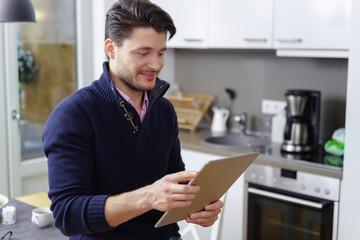 mann steht in der küche und schaut auf sein tablet