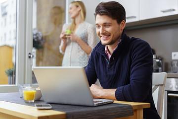 mann sitzt am küchentisch und bestellt im internet