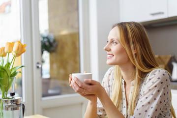 entspannte frau mit einer tasse tee schaut lächelnd aus dem fenster