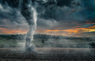 Black tornado funnel over field during thunderstorm. Apocalypse scenario.