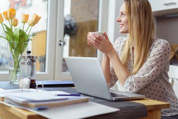 studentin arbeitet zuhause am küchentisch und macht eine pause mit einer tasse kaffee