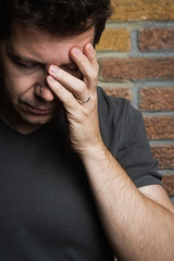 White middle-age male holds one hand to head in despair or pain