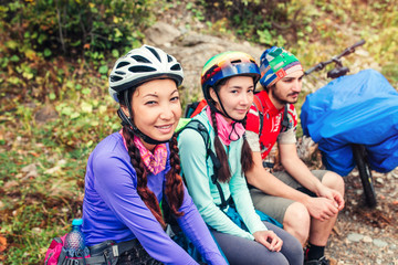 Hiking in mountains. Three bikers sitting on mountain serpentine dirt road.