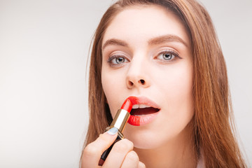 Charming tender  woman in bathrobe doing makeup with red lipstick