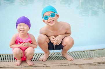 Children in swim suit sitting at swim pool