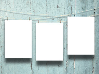 Close-up of three hanged paper sheets with pegs on weathered aqua wooden boards background