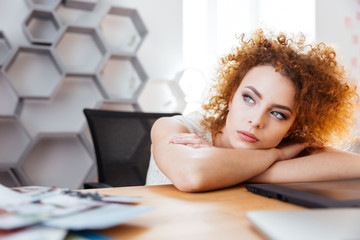 Attractive thoughtful woman designer sitting and dreaming on workplace