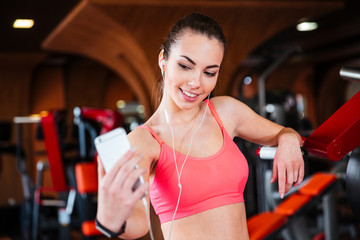 Happy sportswoman listening to music and making selfie with smartphone