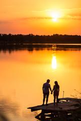couple in love back light silhouette at lake sunset full length