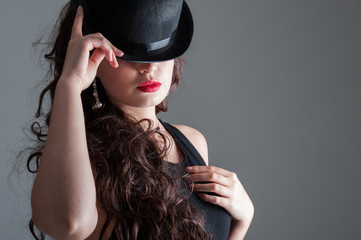 Young lady holding bowler hat with bright strong make up and curly long brunette hair
