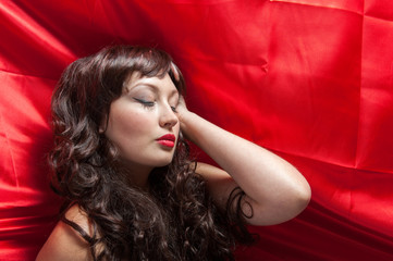 young lady with long brunette curled hair laying on red satin cloth