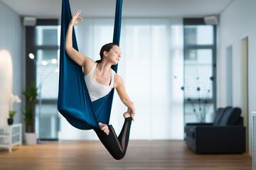Junge Frau macht Aerial Yoga