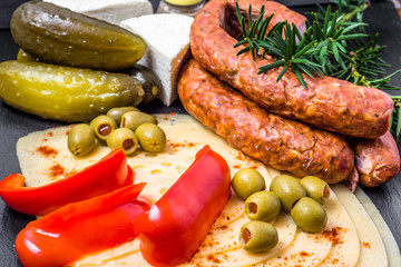 Ingredients of breakfast with cheese slices, sausage and vegetab
