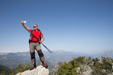 Hiker taking selfie on top of the mountain.