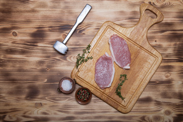Fresh meat steaks on light wooden cutting board