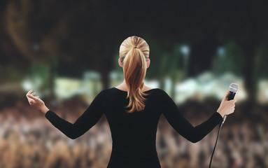 Donna su palco folla microfono canta