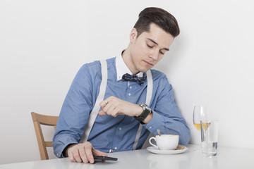 Mann sitzt bei einem Glas Wein und einer Tasse Kaffe und schaut