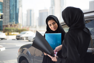 Two Middle Eastern Emirati Businesswomen Discuss Something next to a Car