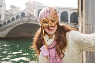 Smiling woman with Venice Mask near Rialto Bridge taking selfie
