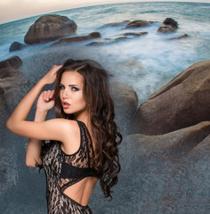 Beautiful young brunette woman against rocky shore or beach