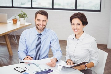 Happy business people with documents sitting in office