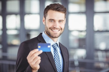 Happy businessman showing credit card