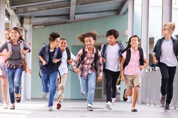 Group of elementary school kids running in a school corridor