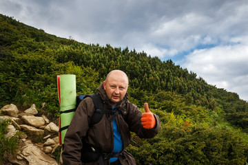 Portrait of male backpacker with a rucksack standing on the mountain and shows thumb up, Carpathians, Ukraine