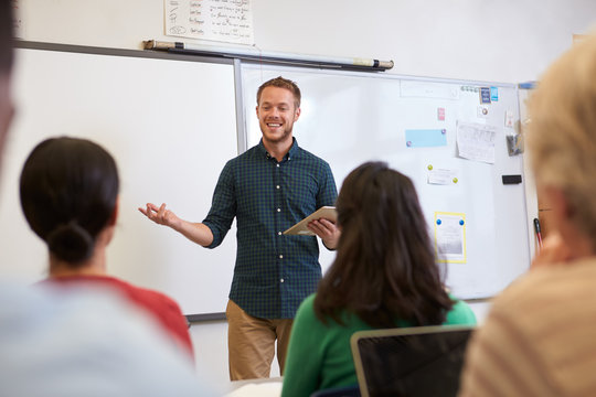 Male teacher listening to students at adult education class