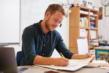 Young bearded male teacher at desk marking students' work