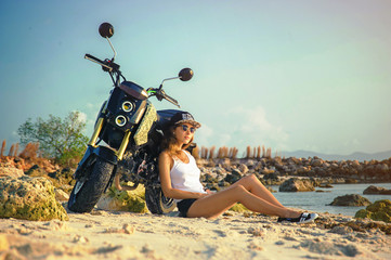 Young sexy girl on a beach with the motorcycle