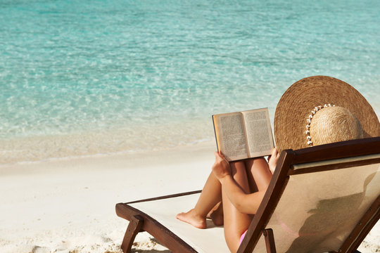 Young woman reading a book at beach