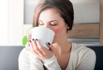 Woman with cup of tea in kitchen