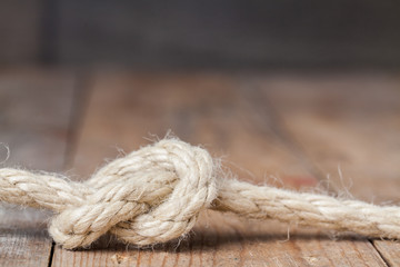 Old frayed rope twisted and tied in a bundle on a rough wooden background
