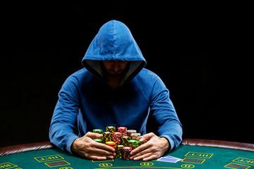 Poker player taking poker chips after winning