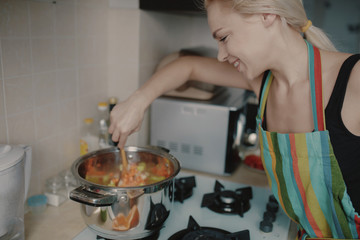 Young woman preparing pumpkin soup