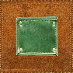 Green blank leather label stitched onto orange leather surface